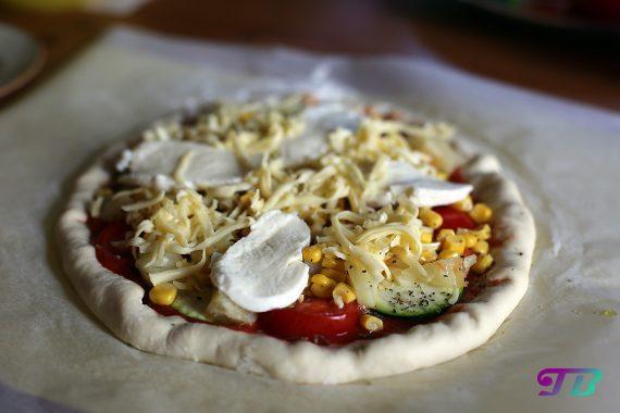 Vegetarische Pizza mit Tomaten, Zucchini, Mais, Käse und Mozarella
